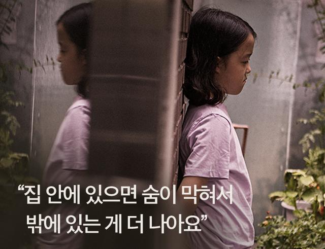 벽에 기대어 서있는 아동의 이미지